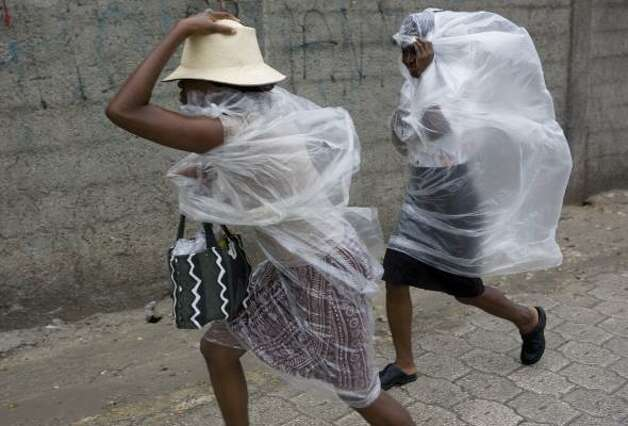 People use plastic sheeting to cover themselves from rain caused by Hurricane Gustav in Port-au-Prince, Haiti, Aug. 26. Photo: Ariana Cubillos, AP