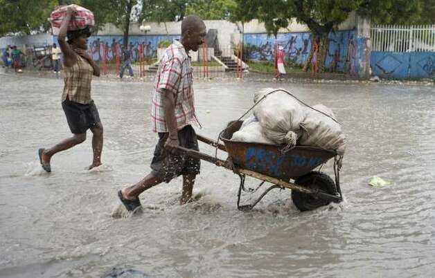 People carrying belongings cross a street flooded by rain caused by Hurricane Gustav in Port-au-Prince, Haiti, Aug. 26. Photo: Ariana Cubillos, AP