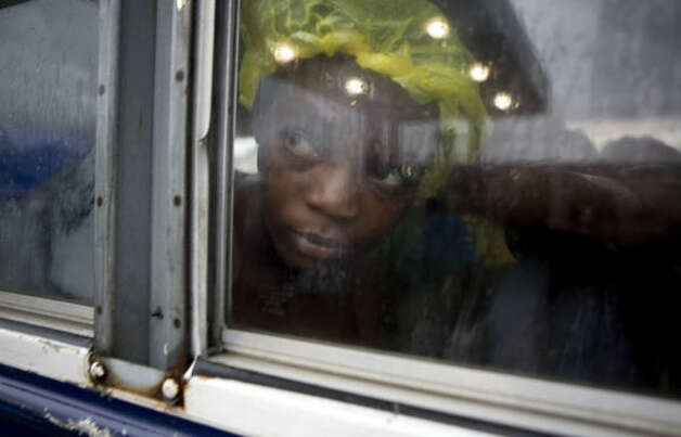 A girl looks through a bus window as it rains in Port-au-Prince Aug. 25. Photo: Ariana Cubillos, AP