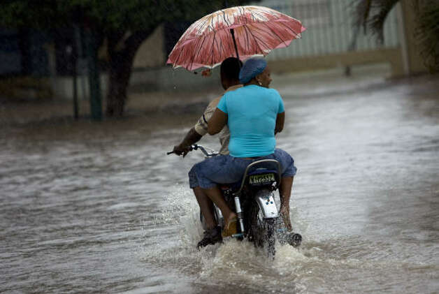 A woman uses an umbrella as she rides on the back of a motorcycle through a flooded street caused by rain from Tropical Storm Gustav in Santo Domingo Aug. 25. Photo: Ramon Espinosa, AP