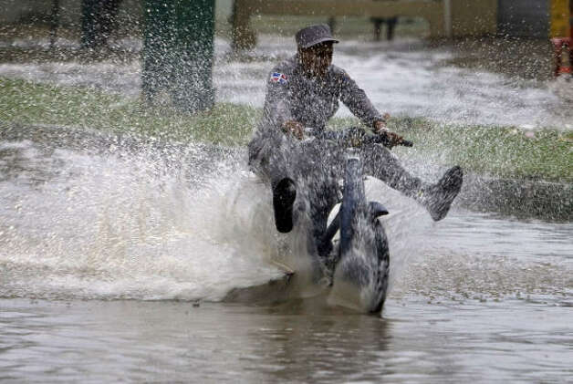 A Dominican police officer rides his motorcycle through a flooded street caused by rain from Tropical Storm Gustav in Santo Domingo Aug. 25. Photo: Ramon Espinosa, AP