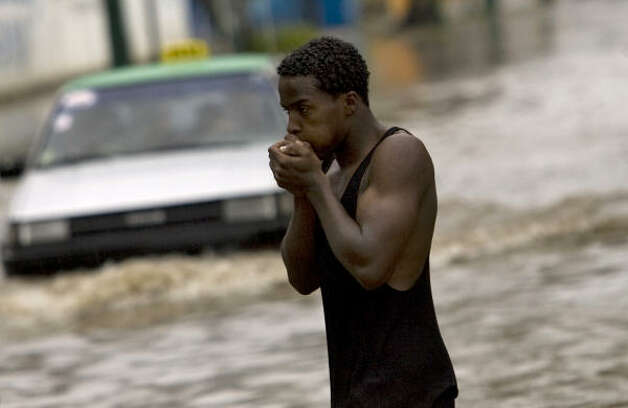 A man stands in a street flooded by rain caused by Tropical Storm Gustav as a car drives through it in Santo Domingo, Aug. 25. Photo: Ramon Espinosa, AP
