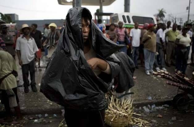 A woman covers herself from the rain with a plastic bag at a bus station in Port-au-Prince Aug. 25. Photo: Ariana Cubillos, AP