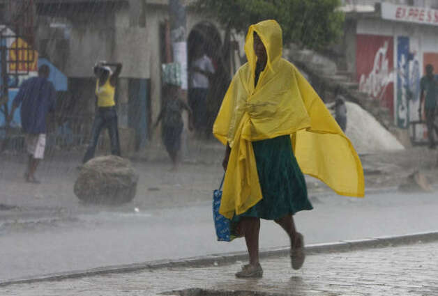 A woman uses a poncho to keep dry as she walks through rain caused by Tropical Strom Gustav in Port-au-Prince. Photo: Ariana Cubillos, AP