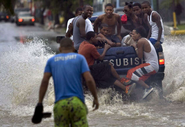 People ride in the back of a truck through a flooded street caused by rain from Tropical Storm Gustav in Santo Domingo Aug. 25. Photo: Ramon Espinosa, AP