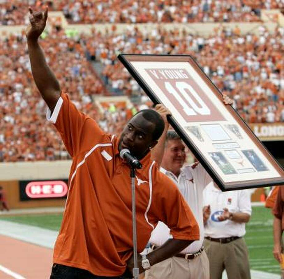 "Vince Young gives a ""Hook 'Em Horns"" as his number is retired in a pre-game ceremony. Coach Mack Brown holds the frame of the now-retired number. Photo: Harry Cabluck, AP"
