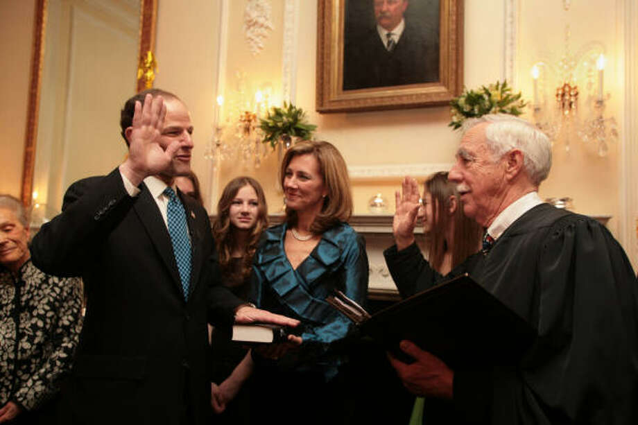 Eliot Spitzer, second from left, is officially sworn in  as governor of New York at midnight by U.S. District Court Justice Robert W. Sweet at the Governor's Mansion in Albany today. His wife Silda, center, and daughters Sarabeth and Jenna, right, watch the ceremony. Photo: James Estrin, AP