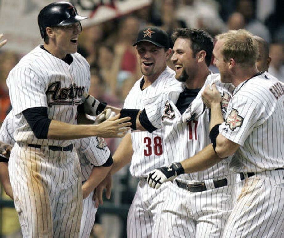Astros first baseman Lance Berkman (second from right) is congratulated by teammates Hunter Pence, left, Brian Moehler (38) and Darin Erstad on his first career walk-off home run helped the Astros defeat the St. Louis Cardinals 3-2 on Thursday night at Minute Maid Park. Photo: Pat Sullivan, AP