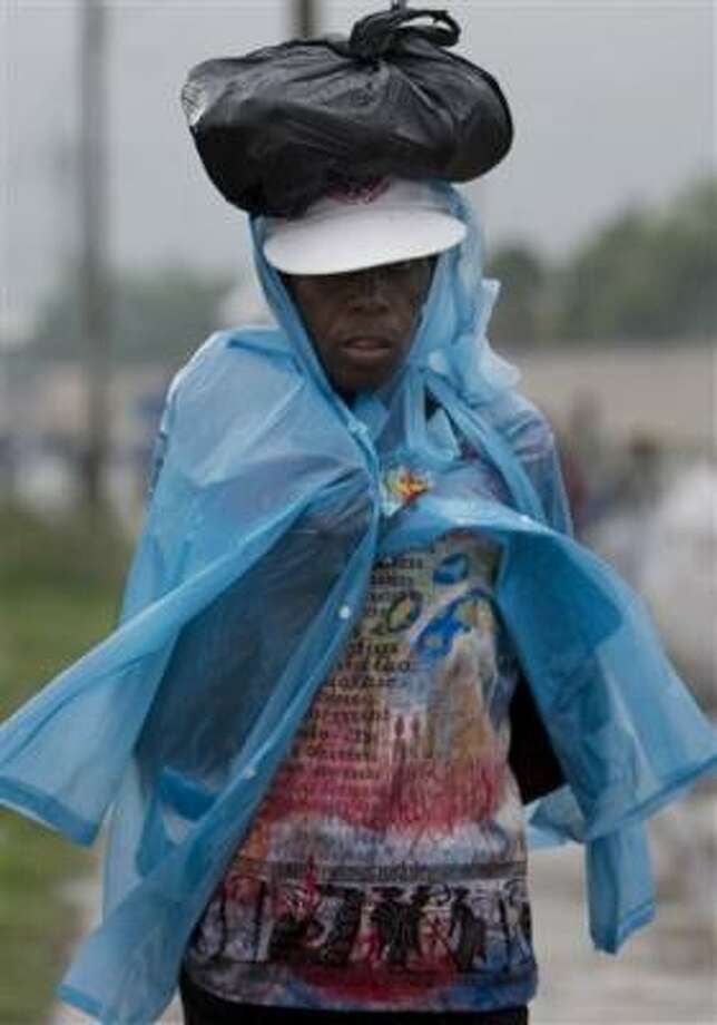 A woman uses a poncho to keep dry as she walks through rain caused by Tropical Strom Gustav in Port-au-Prince Aug. 25. Photo: Ariana Cubillos, AP