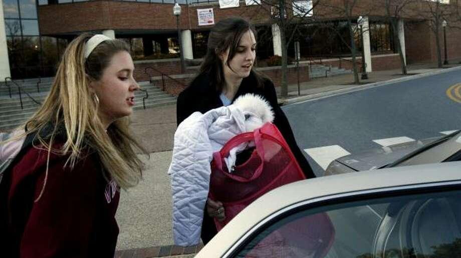 Emily Block, right, helps Virginia Tech freshman Megan Bowen load clothes into her car Monday. Bowen's mother decided she should come home to Poquoson, Va. Photo: JASON ARTHURS, NEWS & OBSERVER / ASSOCIATED PRESS