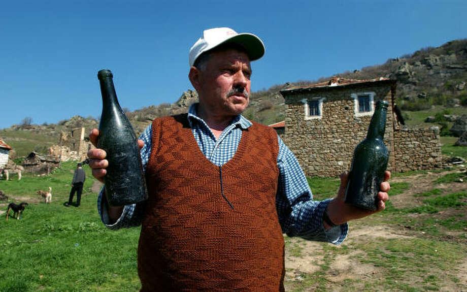 Najdo Koleskovski, a 56-year-old cattleman, shows empty old bottles unearthed nearby in the southern Macedonia village of Gruniste. Photo: BORIS GRDANOSKI, AP