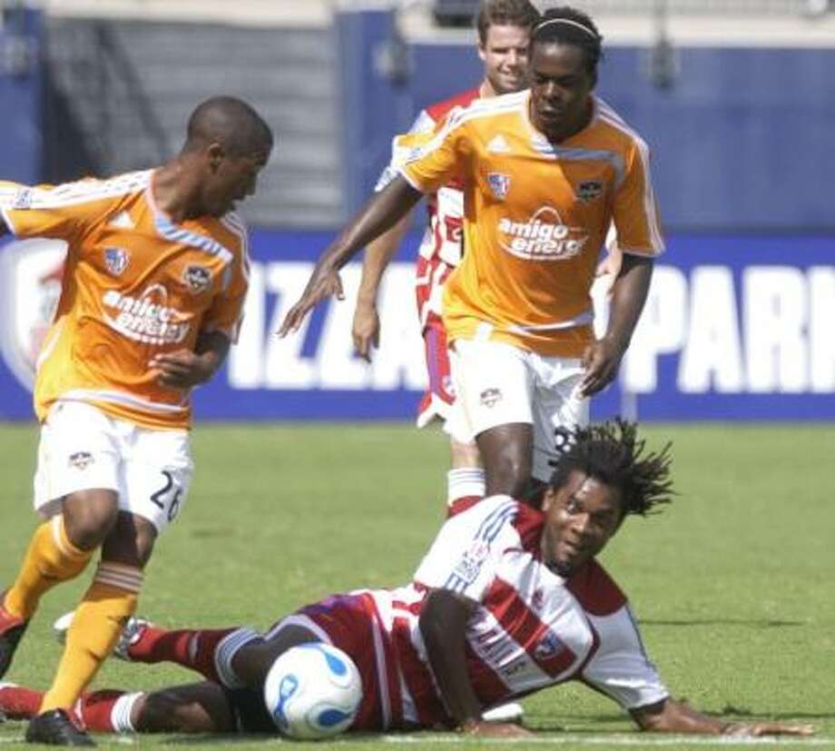FC Dallas' Adrian Serioux gets off a pass while on the ground as Corey Ash, left, and Joseph Ngwenya close in. Photo: Juan Garcia, AP