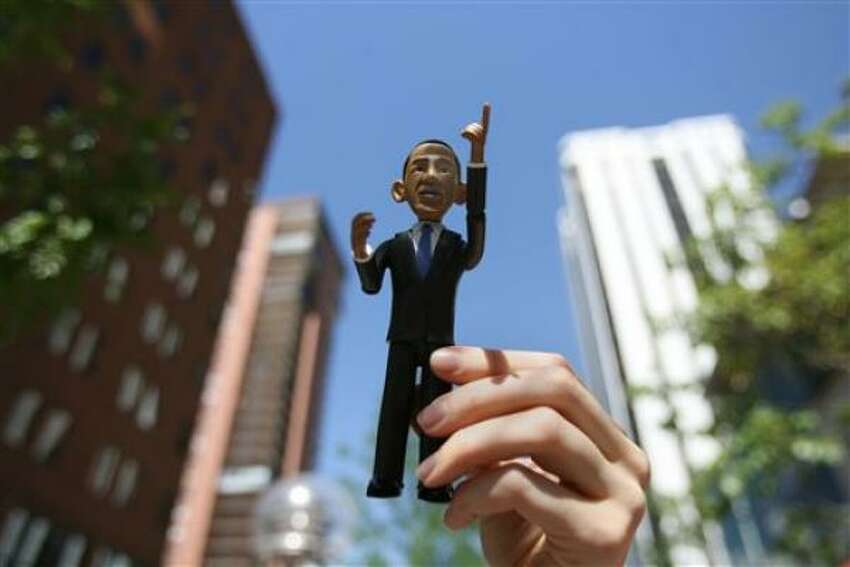 Alyssa Zeller holds an action figure in the likeness of Sen. Barack Obama Monday in Denver. Thousands of visitors are in Denver for the Democratic National Convention.