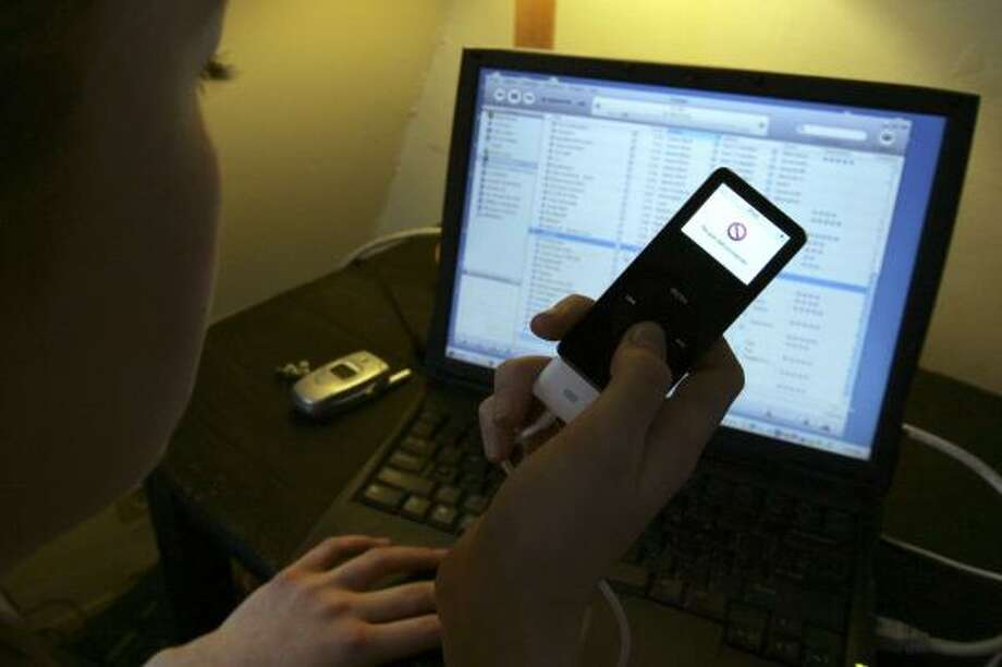 An iPod user downloads digital files from a computer. While most music consumers still buy CD albums, that segment of the industry is declining, while digital singles are rising. Photo: JACQUES BRINON, ASSOCIATED PRESS FILE
