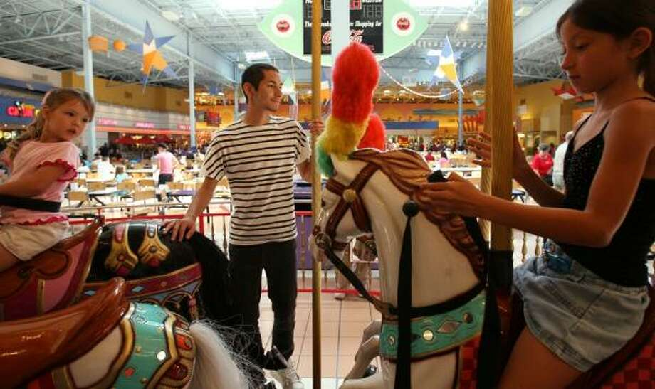 Sam Dyke, 17, checks to make sure children are secure on the Island Carousel at Katy Mills Mall. Dyke said he started looking for work this spring. Getting ready to ride the carousel Saturday are Madisyn Dixson, 3, of Houston, left, and Nicole Mendoza, 7, of Stafford. Photo: SHARÓN STEINMANN, CHRONICLE