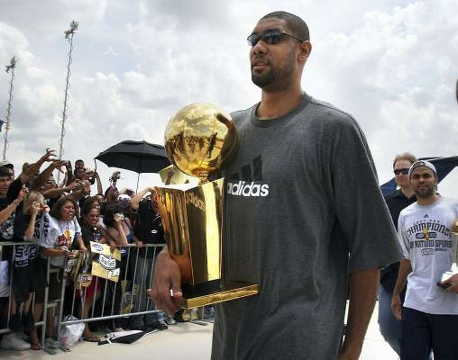 Tim Duncan carries the NBA championship trophy as he and Spurs guard Tony Parker, right, arrive to a heroes' welcome at San Antonio International Airport on Friday. Photo: BOB OWEN, ASSOCIATED PRESS