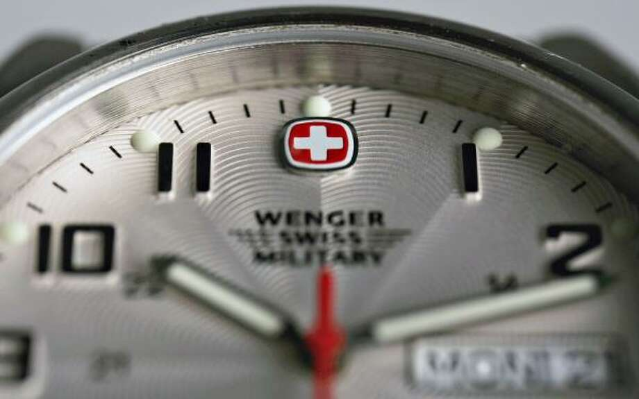 The white cross logo on a red background of Switzerland's flag appears on a Wenger Swiss Military watch face. About 40 million fake Swiss watches are made worldwide each year, compared with 25 million authentic timepieces. Photo: DANIEL ACKER, BLOOMBERG NEWS
