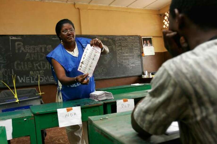 A poll worker holds an election ballot on Saturday during vote counting at a polling station in Freetown, Sierra Leone. Photo: REBECCA BLACKWELL, AP