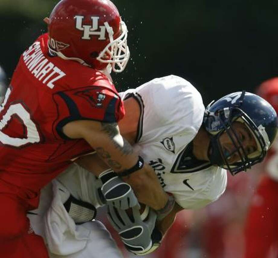 Rice's James Casey absorbs the kind of punishment Houston safety Rocky Schwartz dishes out on a regular basis. Photo: KEVIN FUJII, CHRONICLE