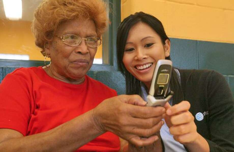 AT&T employee Sarin Mou, right, shows Odia Mathews functions on her cell phone Wednesday at the Sunnyside Community Center. Photo: BILL OLIVE, FOR THE CHRONICLE