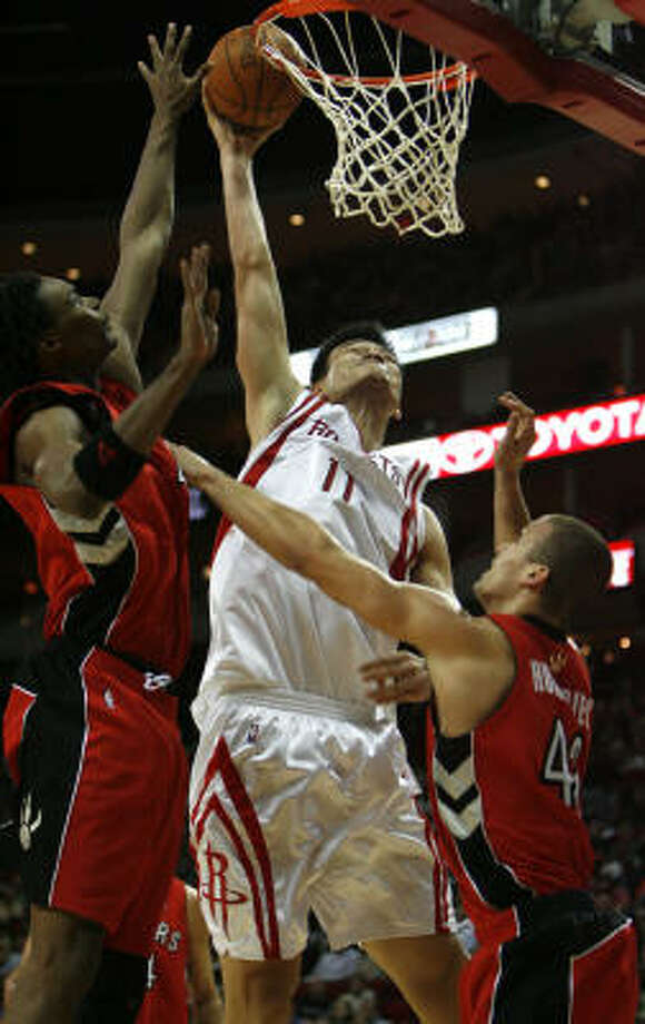 Yao Ming is blocked at the basket by the Raptors' Kris Humphries (right) and Chris Bosh in the fourth quarter of a 91-79 Rockets win on Saturday night. Photo: Sharon Steinmann, Chronicle