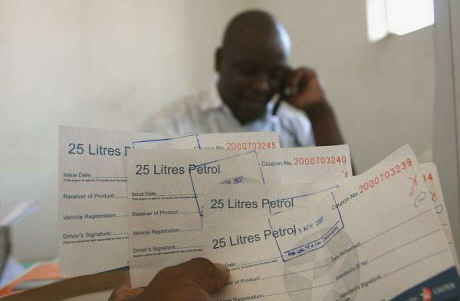 A man inspects his fuel coupons in Harare. Zimbabweans abroad are using the Internet to buy goods online for friends and family back home in a country hurt by inflation and shortages. Photo: ASSOCIATED PRESS