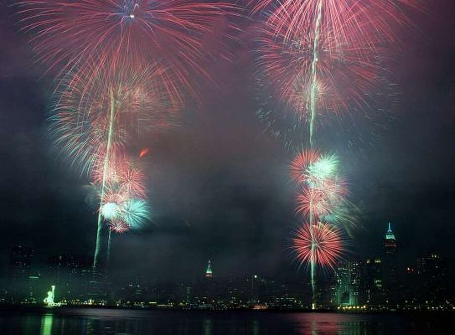 With Manhattan's skyline glistening in the background, Fourth of July fireworks explode high over New York's East River. Photo: BEN GARVIN, ASSOCIATED PRESS