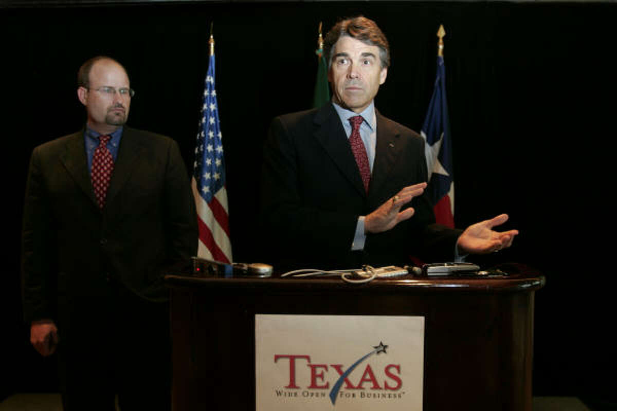 With Texas Secretary of State Phil Wilson at left, Perry says Congress lacks the