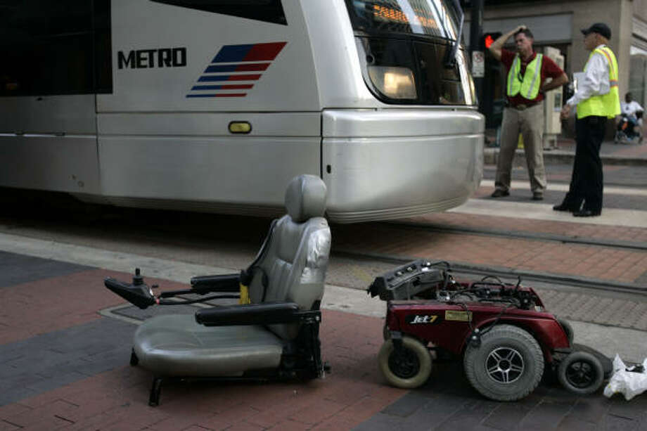 Metro workers stand near a motorized scooter clipped by a train at McKinney and Main. The rider was taken to St. Joseph's Hospital for treatment of minor injuries, officials said. Photo: Johnny Hanson, For The Chronicle