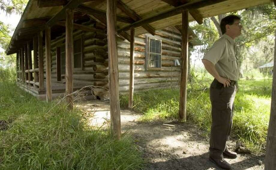 Stuart Marcos, manager for the Trinity River National Wildlife Refuge, stands near the old hunting lodge on land that the U.S. Fish and Wildlife Service is in the process of buying. Photo: BRETT COOMER, CHRONICLE