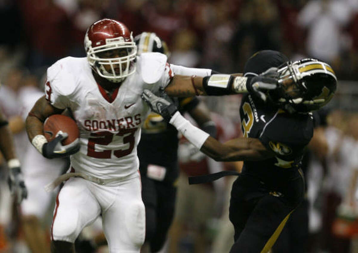 Oklahoma running back Allen Patrick gives Missouri defender Darnell Terrell a stiff arm and runs for big yards in the third quarter.