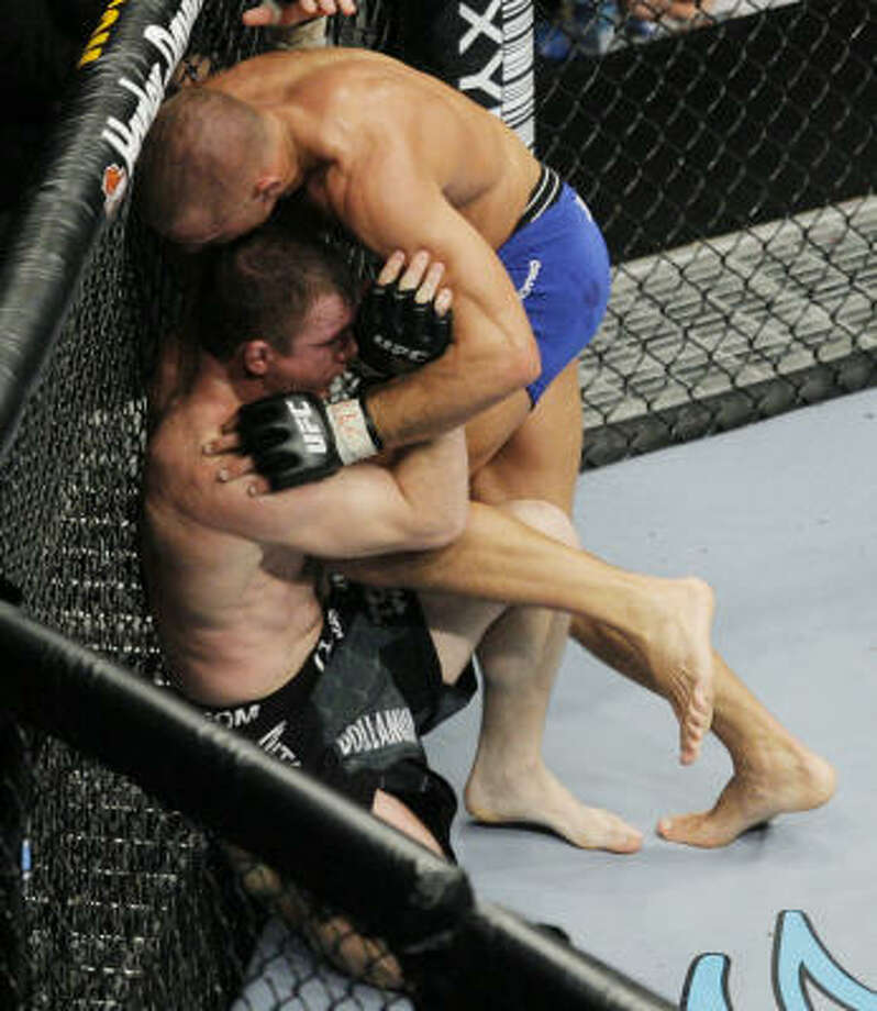 Georges St. Pierre, top, lands a knee kick to the body of Matt Hughes during the second round of their welterweight bout at UFC 79. St. Pierre won by submission later in the round. Photo: Jae C. Hong, AP