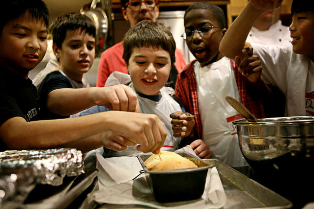 Instructor Julie Hewitt, in the background, keeps a watchful eye on her students, from left, Phillip Wong, 11; Zachary Birenbaum, 11; Aaron Birenbaum, 9; Jerry Riggins, 13; and Daniel Wong, 13, as they check to see if a cake is done during a cooking class at Central Market in Houston.