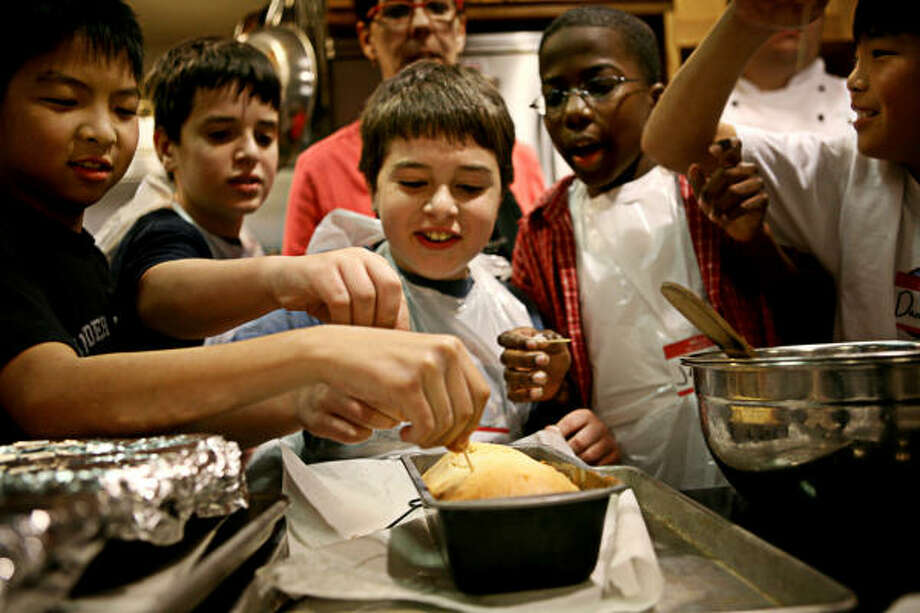 Instructor Julie Hewitt, in the background, keeps a watchful eye on her students, from left, Phillip Wong, 11; Zachary Birenbaum, 11; Aaron Birenbaum, 9; Jerry Riggins, 13; and Daniel Wong, 13, as they check to see if a cake is done during a cooking class at Central Market in Houston. Photo: ERIN TRIEB, FOR THE CHRONICLE