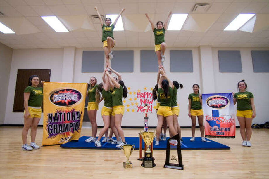 Members of the national champion Spring Woods High School cheerleading team pose for photographs. Holding the National banner;  Elsie Contreras, 17, and Hannah Klim, 16.  The state banner is held by by Brittany Davis, 18, and Katarina Reyes, 16.The left group is Loren Thomas, 17; Sarah Smith, 16; and Angela Masera, 17; the girl at top is Angelica Hernandez, 15.  At right, Violet Diaz, 17, is supported by Sandra Cruz, 18; Brittney Olexa, 17; Dorya Rincon, 18; and Bee Hemmavanh, 18. Photo: R. Clayton McKee, For The Chronicle