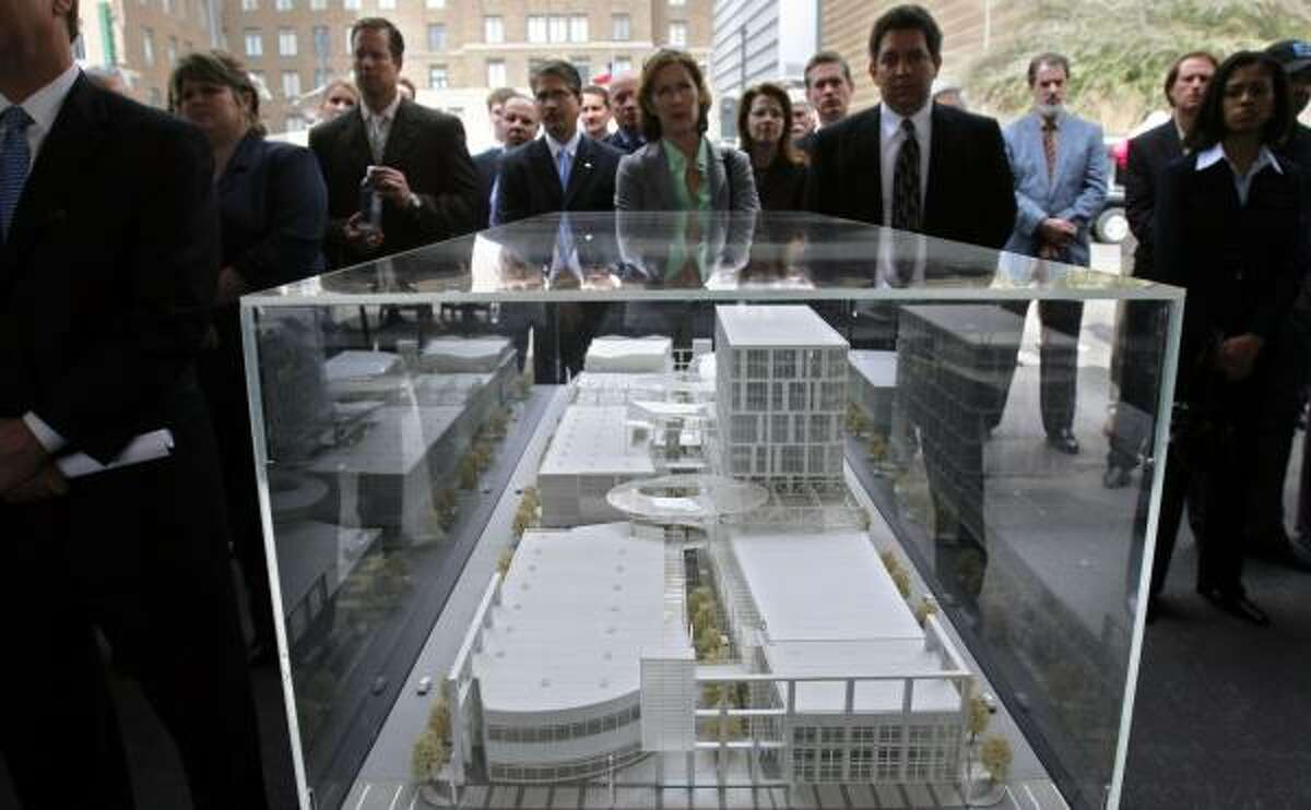 A crowd gathers around the model of the Houston Pavilions development, a $170 million downtown retail, entertainment and office project that is scheduled to open in October 2008.