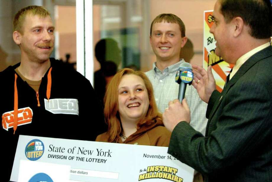 Times Union staff photo by Cindy Schultz     New York Lottery winners Bill Rivenburgh, left, and his wife Alissia, center, join lottery director Robert McLaughlin, right, and Mike Wood of Stewarts, in back, for a news conference Tuesday, Nov. 14, 2006, at the New York Lottery in Schenectady, N.Y. Photo: CINDY SCHULTZ / ALBANY TIMES UNION