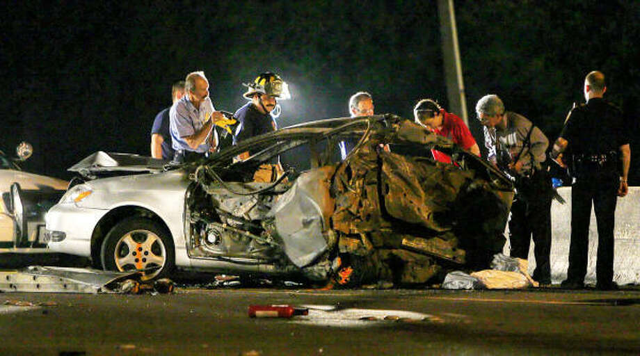 Officials investigate a wreck Saturday night that killed a family of three. Photo: Mayra Beltran, Chronicle