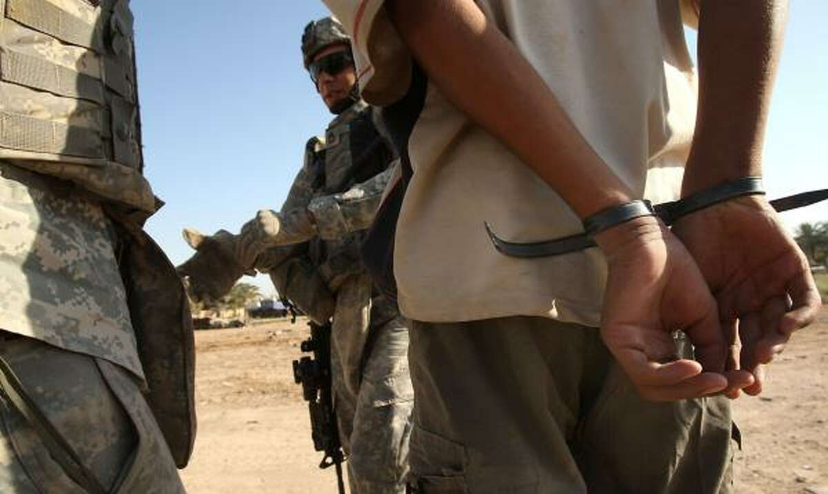 U.S. soldiers detain a boy last month suspected of placing an improvised explosive device in Baghdad's Ghazaliya neighborhood, which has been used as a Sunni insurgent base. Officials say violence there has waned since U.S. and Iraq forces teamed up.
