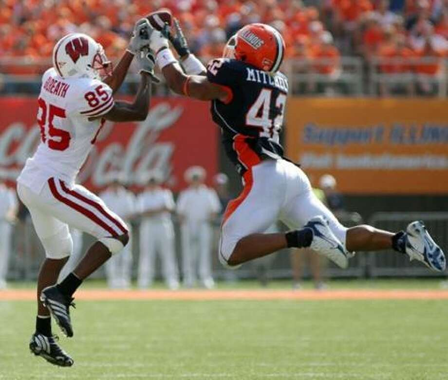 Illinois' Kevin Mitchell, right, breaks up a pass intended for Wisconsin's David Gilreath. Photo: BRAD VEST, ASSOCIATED PRESS