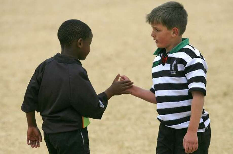 A Soweto rugby club player, left, shakes hand with a player from Johannesburg's Enkuina team. The racial divide that has rocked rugby has faded to a whisper as the nation declares itself proudly South African behind a team which, 13 years after the end of apartheid, remains largely white. Photo: BENEDICTE KURZEN, ASSOCIATED PRESS