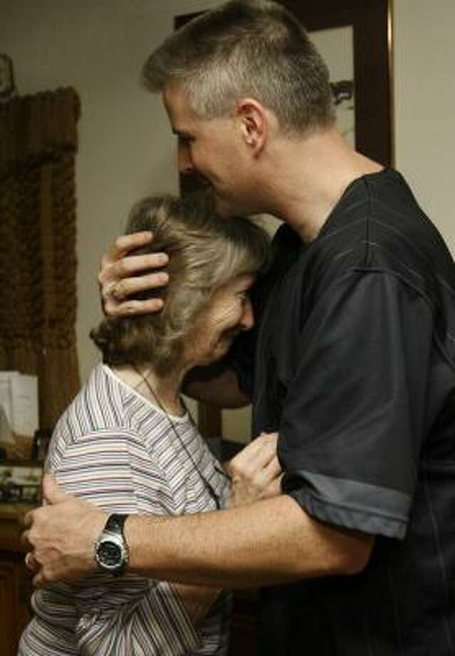 Ty Norling, a deputy constable, hugs his mother, Darleen, on Thursday after she learned about her new furniture. Photo: MELISSA PHILLIP, CHRONICLE
