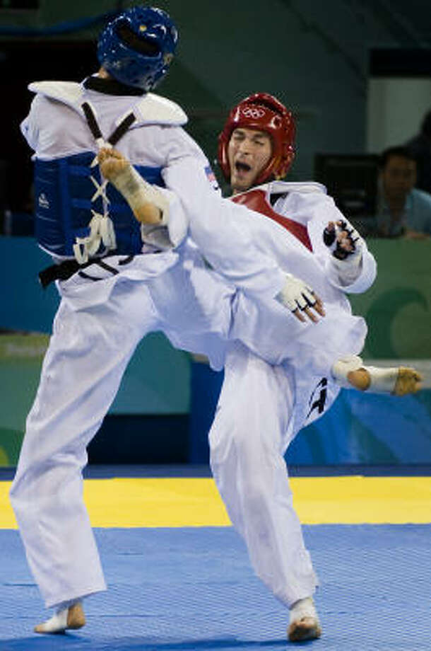 Mauro Sarmiento of Italy, in red, ended the gold medal hopes of Steven Lopez of Sugar Land, as he picked up a point in overtime on this exchange during the  80kg taekwondo quarterfinals at the 2008 Summer Olympic Games on Friday in Beijing. Photo: Smiley N. Pool, Chronicle Olympics Bureau