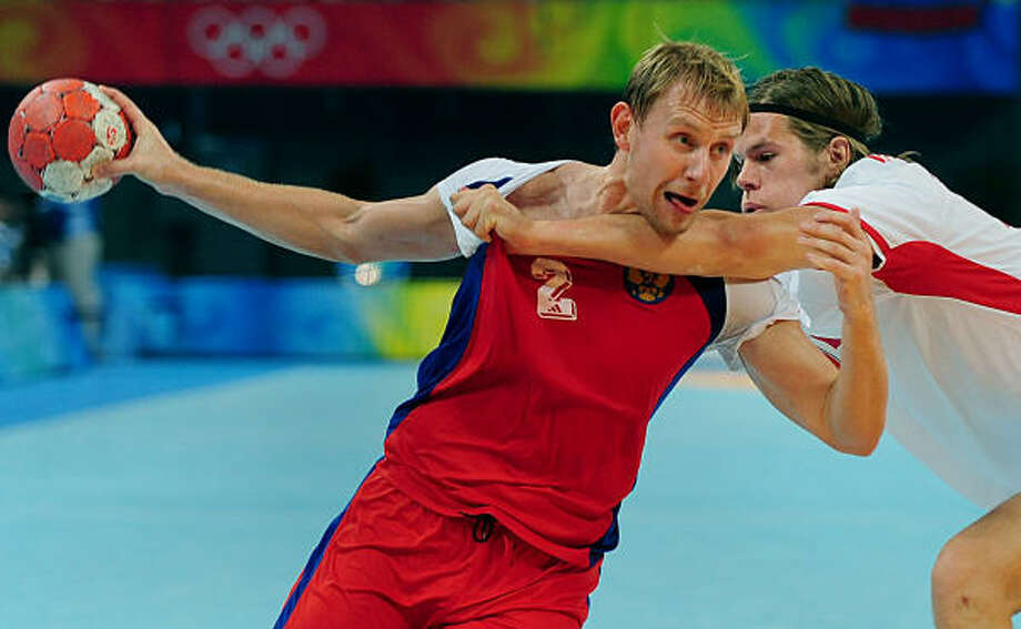 Vasily Filippov of Russia is defended by Mikkel Hansen of Denmark during handball. Photo: Jeff Siner, MCT