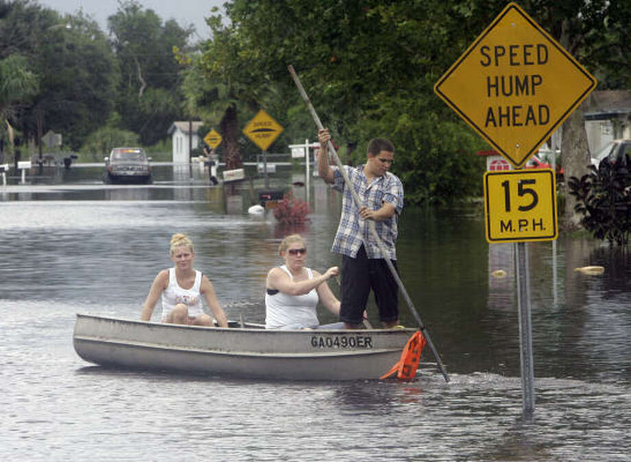 Keira Dreiling, left, Crystal Ellis, center and Greg Meyer make their way down a flooded street in Cocoa, Fla., on Aug. 21. Photo: John Raoux, AP