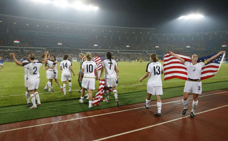 The U.S. women's soccer team celebrates a gold medal win over Brazil by parading the U.S. flag across the stadium Thursday. Photo: Michael Macor, Chronicle Olympic Bureau