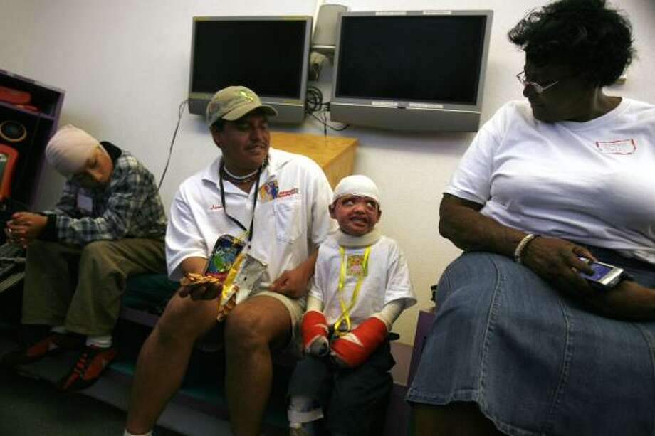 Burn survivor Mauricio Aguilar, 5, center, of Mexico shares a moment with Justina Page during the After Burns Club support group meeting for burn victims and their families organized by Justina Page at Shriners Burns Hospital in Galveston on Aug. 16, in Galveston. To Mauricio's left is his father, Jesus Aguilar, of Mexico, and at far left is Jose Tapia, 13, of Mexico. Page started the Amos House of Faith, named after her son who died in a fire. Photo: Sharon Steinmann, Chronicle