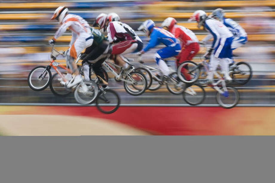 Cyclists are a blur as they hit one of the first jumps off the start, including Conroe's Kyle Bennett. Photo: Smiley N. Pool, Chronicle Olympic Bureau