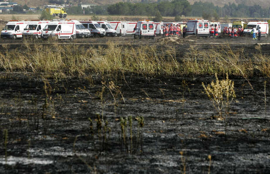 Ambulances and rescue workers gather near the site where a Spanair jet crashed on takeoff at Madrid airport. Photo: Daniel Ochoa De Olza, AP