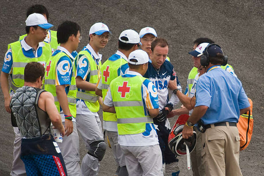 Kyle Bennett (88) of Conroe is helped to his feet as he is attended to by medical teams after a crash during the quarterfinals of BMX cycling. Photo: Smiley N. Pool, Chronicle